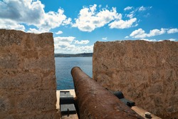 Saint Mary's Battery. Old historic artillery battery from the 18th century with rusted cannons on the island of Comino in Malta. Great view of a cannon barrel and the coastline on a sunny day.