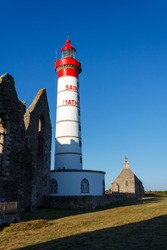 Saint-Mathieu lighthouse and partially view of the ruins of the abbey. White and red lighthouse and blue sky