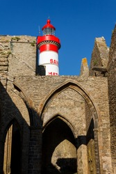 Saint-Mathieu lighthouse top over the ruins of the abbey. White and red lighthouse and blue sky