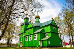 Saint Michael Archangel Orthodox Church in Trzescianka, Eastern Poland. Beautiful green, timber building with golden domes, against a blue cloud-sky background.