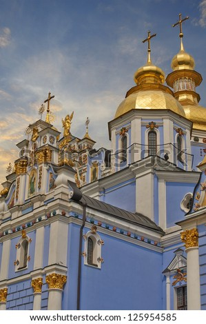 Saint Michael Gilded Russian Orthodox cathedral and a church with wooden dome in snow, Kiev, Ukraine