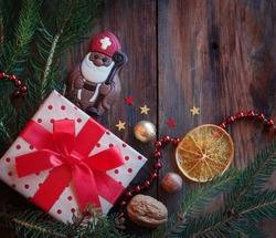 Saint Nicholas and gift on a wooden background with winter decor. Dutch, Belgian holiday 'Sinterklaas'