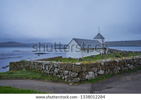 Saint Olav's church on the bank of deep fjord in atlantic ocean in village Kirkjubour on the island Streymoy in Faroe islands. Picture taken in rain and windy scandinavian weather condition in spring.