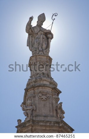 Saint Oronzo on top of his column in the middle of the square in Ostuni. His is called the first bishop of Lecce - Apulia, Italy. - stock photo