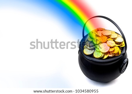 Saint Patrick's Day and Leprechaun's pot of gold coins concept with a rainbow indicating where the leprechaun hid treasure on white with copy space and clipping path