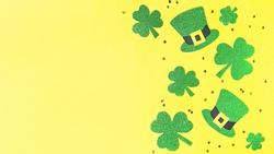 Saint Patrick's day holiday card with green shamrock symbols, hat, golden confetti. Traditional St. Patrick's Day green attire and decorations on yellow background. Web banner, copy space