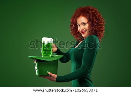 Saint Patricks Day. Young ginger Oktoberfest leprechaun, wearing grenn dress, serving big beer mugs on green background with copy space