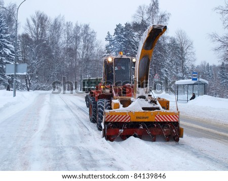SAINT-PETERSBURG, RUSSIA- DECEMBER 12: Snow removal machine with an unidentified driver clean snow-covered road  after cyclone called Monica on December 12, 2010 in Saint-Petersburg, Russia - stock photo