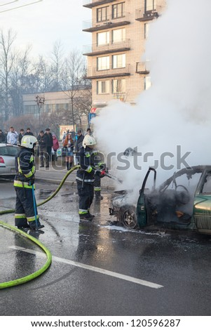 SAINT-PETERSBURG, RUSSIA-NOVEMBER 11,: Firefighters are near burned car on city street on November 11, 2012 in Saint-Petersburg, Russia. Self-ignition car wiring. No one was injured.