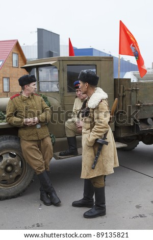 SAINT-PETERSBURG, RUSSIA – NOVEMBER 4: Military performance in celebration of National Unity Day. Three soviet soldiers standing near army lorry on November 4, 2011 in Saint-Petersburg, Russia.