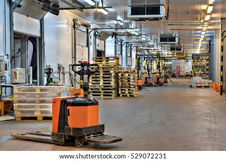 Saint-Petersburg, Russia - October 31, 2016:  electric platform pallet truck in loading  dock area inside cold storage warehouse.