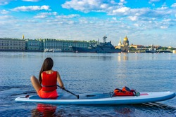 Saint Petersburg. Russia. SUP surfing. Girl sitting on an inflatable Board. Riding on an inflatable Board on the Neva river. Palace embankment. Hermitage. Ships. Isaakievsky cathedral.