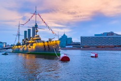 Saint Petersburg. Russia. The cruiser Aurora on the Neva. Museum on the cruiser Aurora. Ship with flags on the background of St. Petersburg. Unusual museums in St. Petersburg. Evening city.
