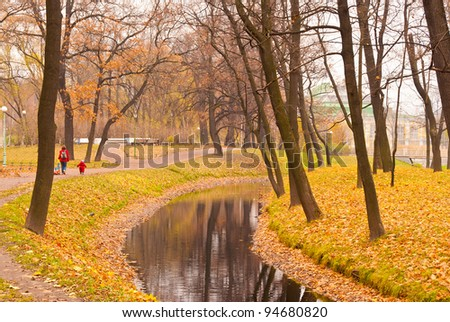 Saint Petersburg Tavrichesky Park view in Autumn pond with building and colorful trees with reflection