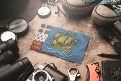 Saint Pierre and Miquelon Flag Between Traveler's Accessories on Old Vintage Map. Tourist Destination Concept.