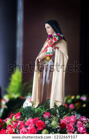 Saint Therese of Child Jesus statue with Thai traditional jasmine garland and pink roses. Picture for art and religion.