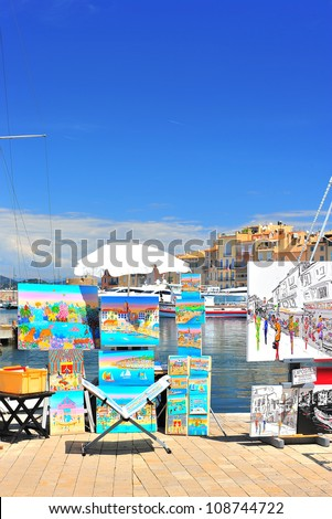 SAINT TROPEZ, FRANCE - MAY 24: View of Saint Tropez harbor with paint art exhibition and sale on May 24, 2012, Saint Tropez. St. Tropez is famous painter city, many prominent painter lived there