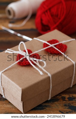 Saint Valentine decoration: handmade crochet red heart for gift paper box. Selective focus
