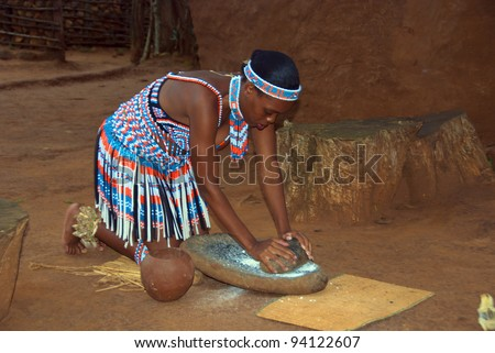 SAKALAND-NOVEMBER 27 :An unidentified young woman wears traditional Zulu clothing, made local beer with wheat on November 27, 2010 Shakaland Zulu Cultural Village, KwaZulu-Natal, South Africa