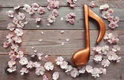 Sakura flowers with petals and music note on wooden