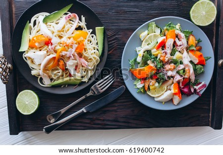 salad and pasta with seafood on wooden background #619600742