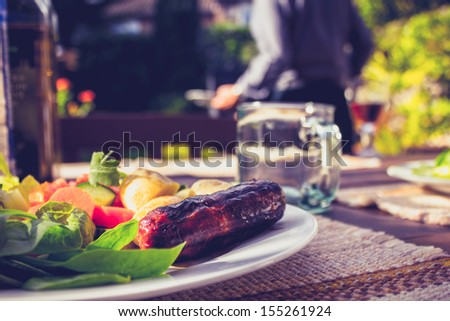 Salad and sausage on sunny day with man in background at barbecue