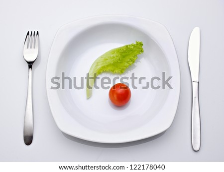 salad and tomato in plate,  fork and knife near plate on  light background