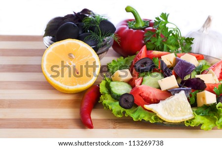 salad and vegetables. Pepper, garlic, lemon and parsley on the board isolated on white background