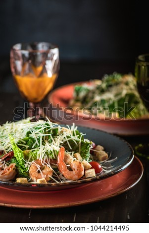 Salad caesar with shrimps or prawn,  croutons, cheese on wooden table. Another salad caesar with chicken in blurred background, glasses of wine and orange juice, dark wall. Place for text or design