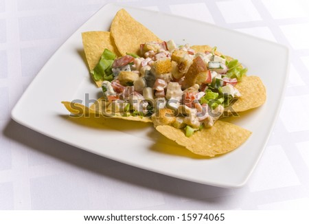 Salad decorated with nachos on white plate