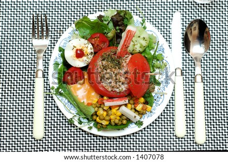 Salad, filled tomato with shrimps. Focus on center of dish.  Healthy snack. Food concept.