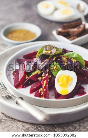 salad from boiled beet, young leaves of spinach and beets with honey-garlic sauce and egg