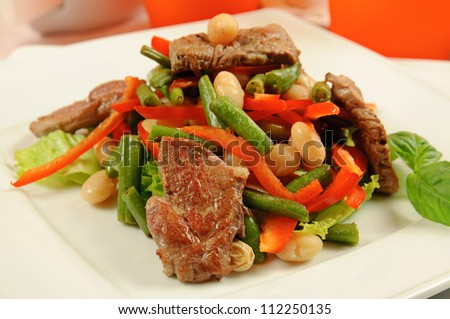 Salad from roasted meat, beans, pepper, lettuce, basil and asparagus in a restaurant