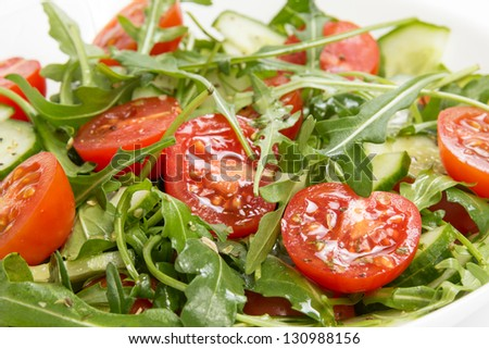 salad from ruccola, cherry tomatoes and cucumber, close up