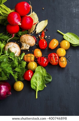 Salad ingredients with organic tomatoes, mushrooms, radish, parsley and spinach with spices - Shutterstock ID 400746898