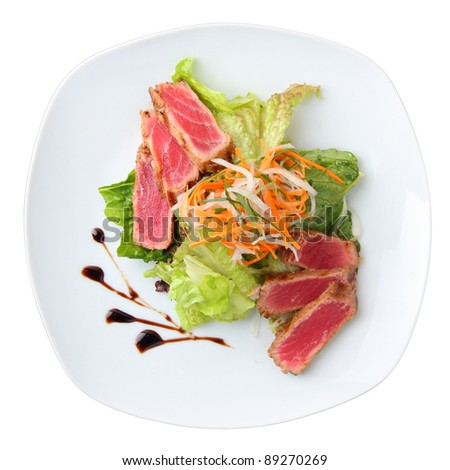 salad maguro sarada with slices of tuna on a white dish isolated on a white background. top view.