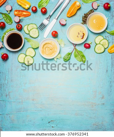 Salad making. Cutlery and dressing ingredients for fresh salad on light blue background, top view place for text. Vinegar ,mustard,oil and honey with chopped vegetables and lettuce leaves.