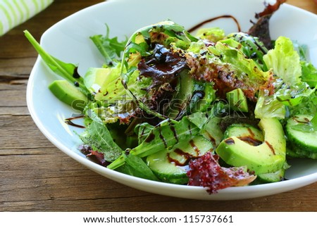 salad mix with avocado and cucumber,  with balsamic dressing - stock photo