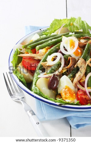 Salad nicoise.  Tuna with eggs, potatoes, green beans, tomatoes, anchovies, onions and black olives.  With vinaigrette dressing.