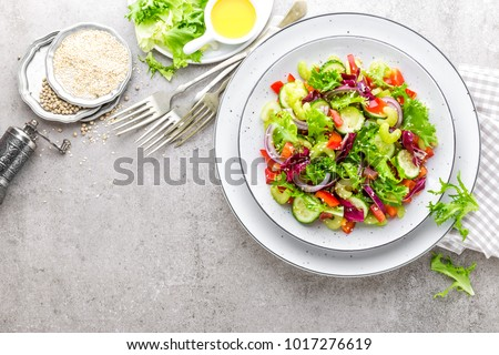 Salad of fresh cucumber, celery, sweet pepper, frize lettuce, red onion and sesame seeds with olive oil. Healthy vegetarian, vegan food. Italian cuisine