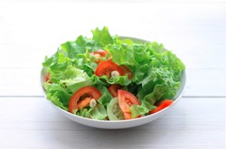 salad of lettuce, tomatoes and cucumbers in a plate on a light wooden background