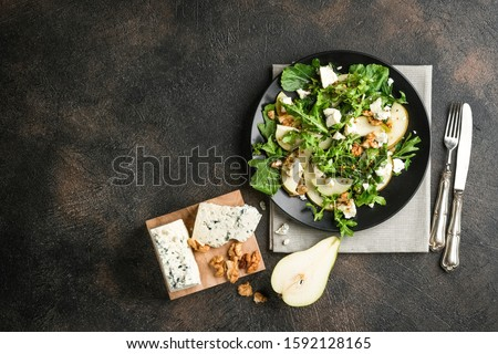 Salad of pear, blue cheese, arugula and nuts with spicy dressing on a dark background. Top view free copy space. Healthy eating. ストックフォト ©