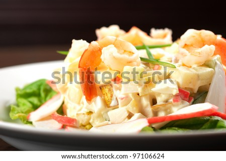 Salad of shrimps, crab meat, cucumbers, apples, potatoes, lettuce, maize, eggs and mayonnaise