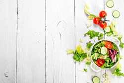 Salad of tomatoes and cucumbers with fresh greens. On a white wooden background.