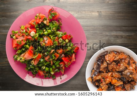 salad of tomatoes, onion, fennel on a pink plate on a wooden background. healthy food.vegetarian food .