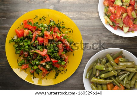 salad of tomatoes, onion, fennel on a yellow plate on a wooden background. healthy food.vegetarian food .