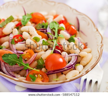 Shutterstock Salad of white beans, tomato, arugula, red onion  and pepper in bowl. Diet food. Healthy lifestyle. Sports nutrition.
