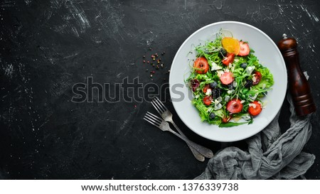 Salad. Salad of arugula, blue cheese, strawberries and blueberries. Top view.