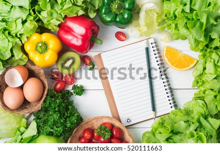 salad vegetables and fruit, tomato, bell pepper, parsley, orange, egg and kiwi fruit with notebook and pencil on wood background and copy space, concept diet and healthy food. #520111663