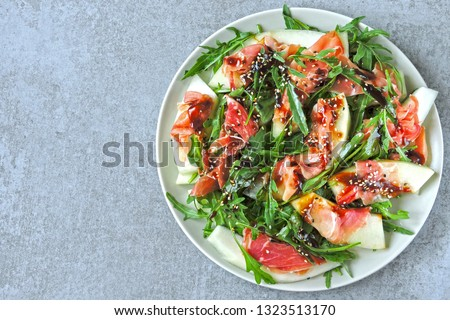 Salad with arugula, melon and prosciutto. Keto diet. Paleo diet. Pegan diet. The concept of a beautiful and delicious diet food.